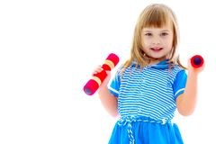 Little girl doing exercises with dumbbells. A cute little girl doing exercises with dumbbells. The concept of strength, health and sport. Isolated on white Stock Images
