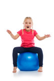 Little girl doing fitness exercise with gym ball. Stock Photos