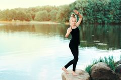 Little girl doing fitness, pilates on the river bank stock images