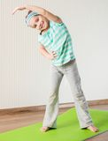 Little girl doing gymnastic exercises. Smiling girl with the fitness ball at home Royalty Free Stock Photo