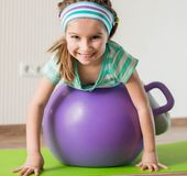 Little girl doing gymnastic exercises. Smiling girl with the fitness ball at home Stock Images
