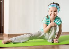 Little girl doing gymnastic exercises. Smiling girl with the fitness ball at home Stock Photo