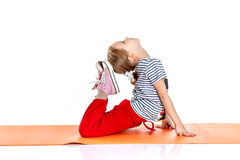 Little girl doing gymnastic exercises on an orange yoga mat. doi. Ng fitness exercises isolated on a white background Royalty Free Stock Photography