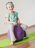 Little girl doing gymnastic exercises. Smiling girl with the fitness ball at home Royalty Free Stock Images