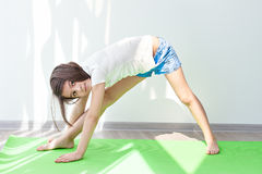 Little girl doing gymnastics on a green mat for yoga Stock Images