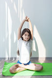 Little girl doing gymnastics on a green yoga mat in the lotus position. Stock Photos