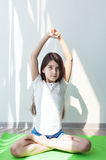Little girl doing gymnastics on a green yoga mat in the lotus position. Stock Images