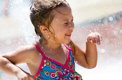 Little girl doing a happy dance. A little girl laughs as she does a 'happy dance' in a city fountain Stock Image