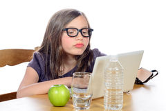 A little girl doing her homework on her computer Stock Images