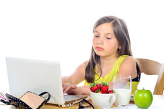 A little girl doing her homework on her computer Stock Photos