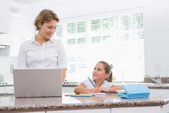 Little girl doing her homework with mother using laptop Stock Photo