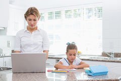 Little girl doing her homework with mother using laptop Stock Photography