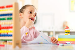 Little girl is doing homework. Stock Photo