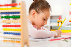 Little girl is doing homework. Royalty Free Stock Photos