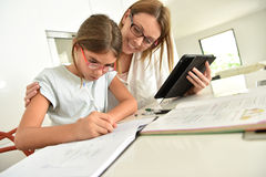 Little girl doing homework with her mother Stock Image