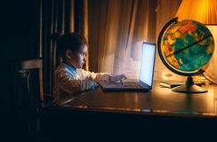 Little girl doing homework on laptop at evening. Portrait of little girl doing homework on laptop at evening royalty free stock images