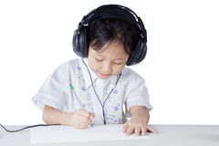 Little girl doing homework while wearing earphones Royalty Free Stock Photos