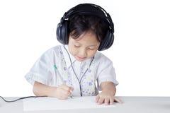 Little girl doing homework while wearing earphones Royalty Free Stock Photos