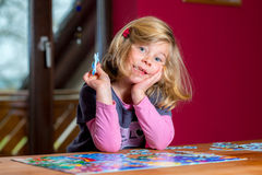 Little girl doing a jigsaw puzzle Royalty Free Stock Photography