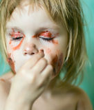 Little girl doing make-up. Little beauty girl doing make-up by herself with mother's cosmetics royalty free stock photo