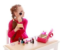Little girl doing make-up sitting at the table Royalty Free Stock Photos