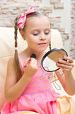 Little girl doing makeup Stock Photo
