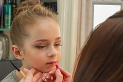 A little girl doing makeup before performing on stage. Preparation before the performance in the dressing room. Makeup artist makes the child makeup in the stock images