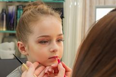 A little girl doing makeup before performing on stage. Preparation before the performance in the dressing room. Makeup artist makes the child makeup in the stock photos