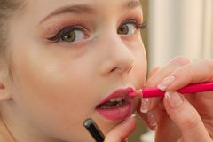A little girl doing makeup before performing on stage. Preparation before the performance in the dressing room. Makeup artist makes the child makeup in the royalty free stock photo