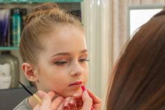A little girl doing makeup before performing on stage. Preparation before the performance in the dressing room. Makeup artist makes the child makeup in the royalty free stock photos
