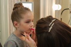 A little girl doing makeup before performing on stage. Preparation before the performance in the dressing room. Makeup artist makes the child makeup in the royalty free stock photography