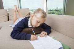 Little girl doing mathematics homework on sofa Stock Photo
