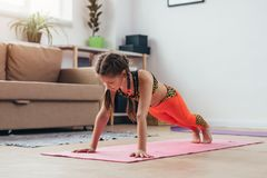 Little girl doing plank exercise at home. Royalty Free Stock Photos
