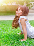 Little girl doing push-ups outdoors Royalty Free Stock Image