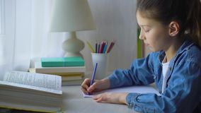 Little girl doing school assignment at home stock video
