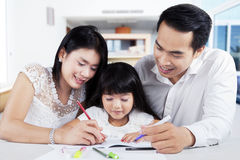 Little girl doing schools task with parents Stock Photography
