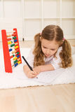 Little girl doing simple math exercises. Laying on the floor with an abacus Stock Photography