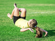 Little girl doing somersault and Lost balance. Athletic little girl falling on green grass Stock Image