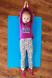 Little girl is doing stretching exercise  on a mat. Children activity. Little girl is doing stretching exercise  on a mat Stock Image