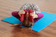 Little girl is doing stretching workout on a mat. stock image