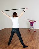 Little girl is doing workout with a stick with a trainer at the stock images