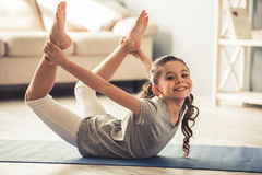 Little girl doing yoga. Charming little girl is looking at camera and smiling while doing yoga at home Stock Photography
