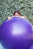Little girl doing yoga exercise. Little cute girl doing exercises with ball outdoors Royalty Free Stock Images