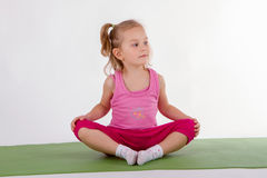 Child is doing yoga. Little girl doing yoga exercises on the mat, isolated on white background Royalty Free Stock Photography