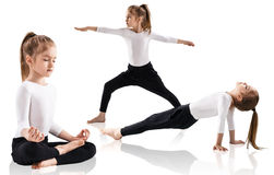 Little girl doing yoga exercises. Over white background Stock Images
