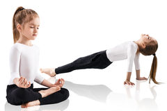 Little girl doing yoga exercises. Over white background Stock Image