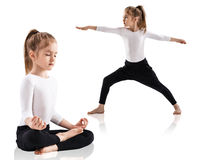 Little girl doing yoga exercises. Over white background Stock Photos