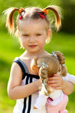 Little girl with doll. Little girl holding her doll in the park Royalty Free Stock Image
