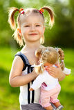 Little girl with doll. Little girl holding her doll in the park Stock Photography