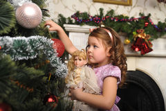 Little girl with a doll in hands. Stock Photos